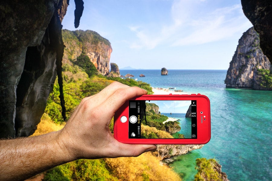 iphone taking picture of sea and cliff landscape
